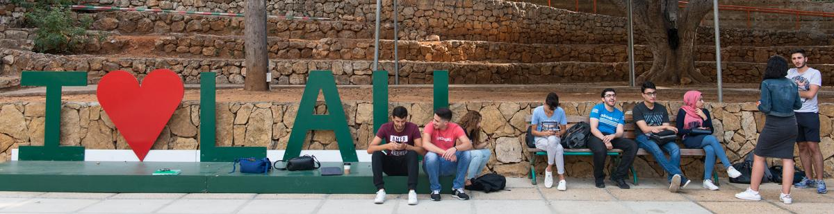 "Students chatting next to a sign that reads ""I love LAU."""